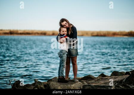 Portrait of sisters hugging on a rock near a lake - Stock Photo