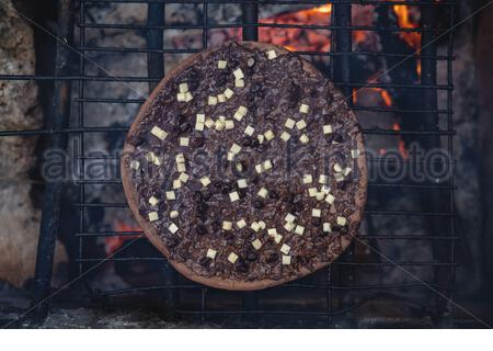 Pizza of three chocolates being cooked on a barbecue with the fire going and smoke coming out - Stock Photo