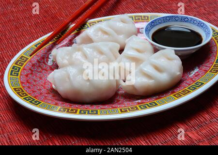 Dim Sum, filled dumplings on plate with chopsticks and soy sauce, Germany - Stock Photo