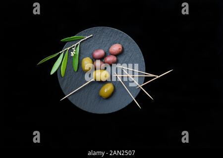 Green and black olives with toothpick on black plate, Germany - Stock Photo