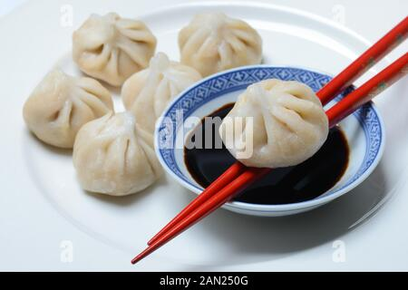 Dim Sum, filled dumplings and bowl with soy sauce, red chopsticks, Germany - Stock Photo