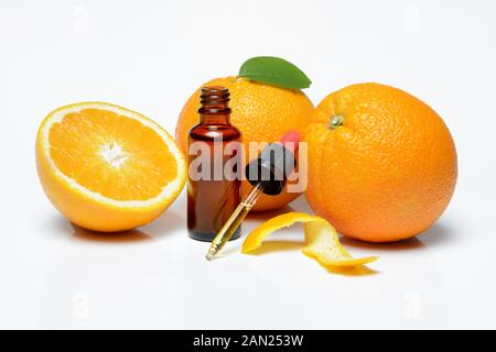 Oranges, halved with peel, orange oil in bottle with pipette, Germany - Stock Photo