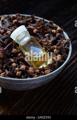 Cloves in a bowl and clove oil, clove oil, Germany - Stock Photo