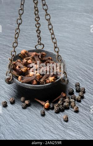 Cloves and peppercorns in a weighing pan, Germany - Stock Photo