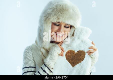 smiling elegant woman in white striped sweater, scarf and ear flaps hat hugging cute hot water filling warmer isolated on winter light blue background