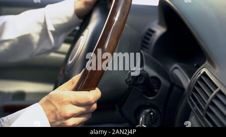 Professional chauffeur driving car for client, close up on wheel, taxi service - Stock Photo