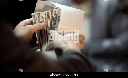 Envelope with dollars, lady giving bribe to politician to cover illegal business - Stock Photo