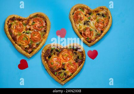 Three pizza in the form of a heart on a blue background with red hearts. Order pizza for a romantic dinner on Valentine's Day. Love.- - Stock Photo