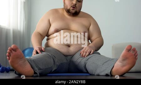 Chubby bare-chested man doing stretching exercise sitting on fitness mat at home - Stock Photo