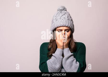 Young woman in gray sweater hat scarf sneezing or coughing, covering mouth with palm isolated on grey background. Healthy lifestyle ill sick disease t - Stock Photo