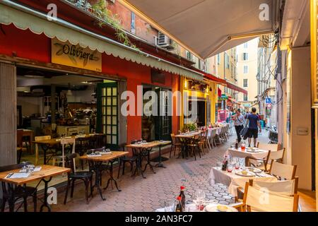 Tourists shop a very narrow alley full of cafes and shops in the Old Town of Vieux Nice, France, on the French Riviera. - Stock Photo