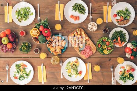 Big festive table with a huge amount of delicious, healthy food. Festive table set for six people. Wooden background top view mock-up. Wooden backgrou - Stock Photo