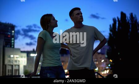 Young man and woman seriously talking, evening leisure time in city, friends - Stock Photo