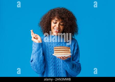 Cute and silly hopeful young african-american woman in sweater, with curly afro haircut, cross fingers good luck, praying and holding plate with - Stock Photo
