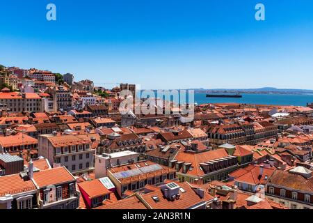 Lisbon rooftops and tanker in river Tagus viewed from Santa Justa lift viewing platform. - Stock Photo
