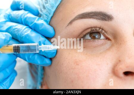 Close-up, beautician makes beauty injections into the skin of a young beautiful girl. Facial care and rejuvenation - Stock Photo