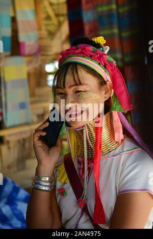 A Padaung woman using her smartphone.