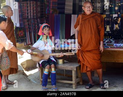 A Padaung woman playing a traditional string instrument. - Stock Photo