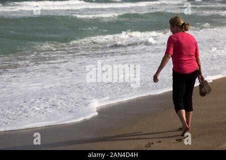 A barefoot woman approaches the frothy surf on this Hutchinson Island beach in Stuart, Florida, USA. - Stock Photo