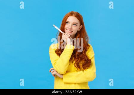 Creative and inspired cute excited redhead woman, journalist or writer creating new ideas, looking upper left corner thoughtful, smiling holding pen - Stock Photo