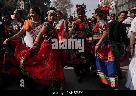 Nepalese women from the Tharu community wearing ethnic outfits sing and dance as they take part during the parade marking the Magh Sankranti or Makar Sankranti festival.Makar Sankranti also known as Maghi, is especially observed by the endogenous groups of Nepal, Tharu, Kirant, Newar. According to culture experts, Tharu and Kirat observe Maghi as their New Year. - Stock Photo