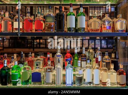 Selection of colorful alcohol bottles on shelves on display at a bar in New York, United States of America, all logos and labels removed - Stock Photo