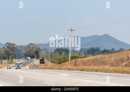 Bushfire smoke from the Gospers Mountain mega-fire covers the mountains behind the Great Western Highway near the town of Hartley in NSW, Australia - Stock Photo