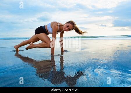 Sporty woman doing mountain climber exercise - run in plank to burn fat. Sunset beach, blue sky background. Healthy lifestyle at tropical island - Stock Photo