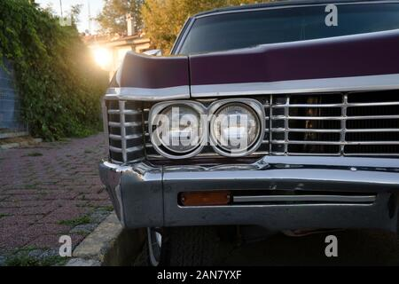 Headlight and front view details of a purple classic american car at street - Stock Photo