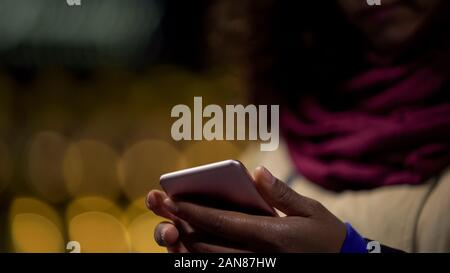 Hands of woman playing in mobile application on her modern gadget, wasting time