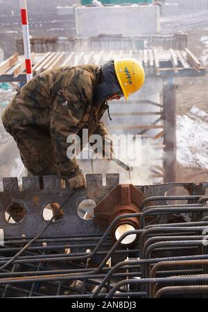 Chinese workers construct piers of a railway over Qingyin (Qingdao-Yinchuan) Expressway in Zouping, Binzhou City, east China's Shandong Province on Ja - Stock Photo