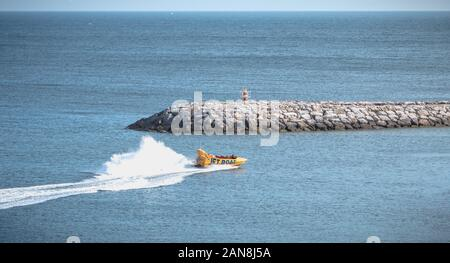 Albufeira, Portugal - May 3, 2018: Jetboat for tourists entering the harbor at full speed on a spring day - Stock Photo