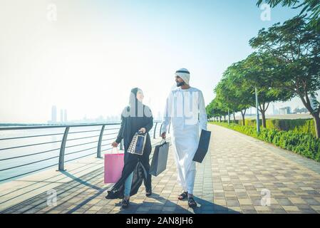 Happy couple walking in Dubai. Man and woman going out for shopping. Concept about relationship in the uae - Stock Photo