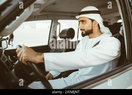 Handsome man with uae traditional outfit driving in Dubai. Middle eastern man with kandura in the car - Stock Photo