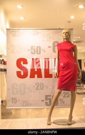 Shop window advertising the Final sale with a discount of 15, 20, 25, 50, 60 percent. Mannequin in a women's red dress on the background of a women's - Stock Photo
