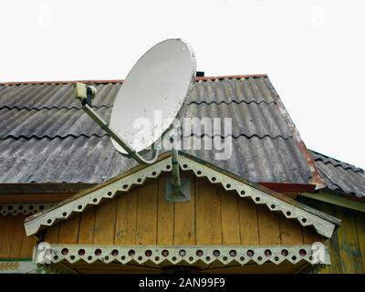 Retro looking satellite dish mounted on a top of old wooden building - Stock Photo