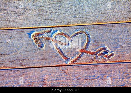 heart and arrow drawn on the frozen surface - Stock Photo