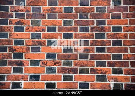 Brick wall background concept with chessboard pattern effect of black and brown bricks shot with wide angle lens - Stock Photo