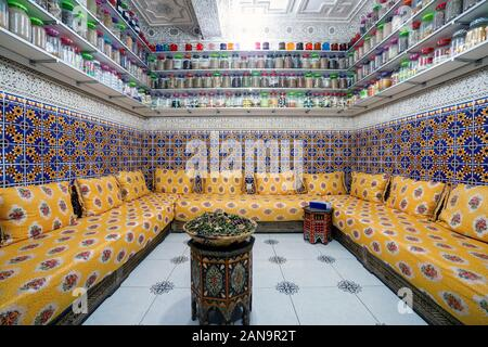 Moroccan interior with variety of spices on shelves and herbal tea in the middle of the room