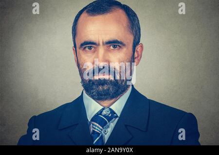 Portrait closeup of a serious middle-aged mature man looking at you camera seriously. Mixed race bearded model isolated on gray studio wall background - Stock Photo
