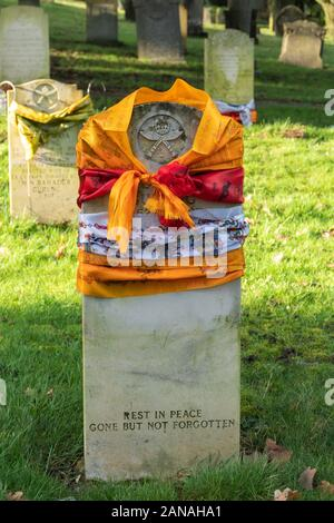 Grave of a Gurkha soldier with the headstone draped with colourful silk scarves, Aldershot Military Cemetery, UK - Stock Photo