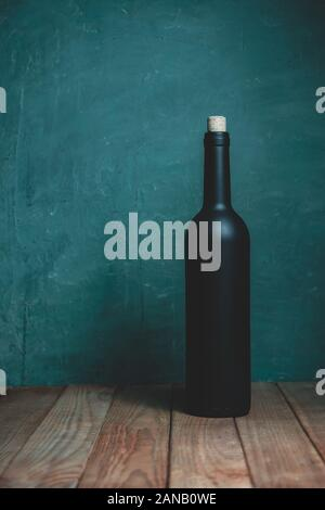 Black Bottlrede wine on a Brown wooden table. Beautiful Green wall background. - Stock Photo