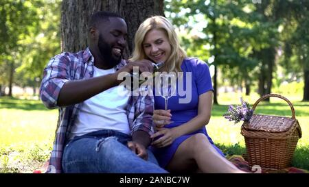 Caring man pouring red wine to womans glass on picnic in park, romantic date
