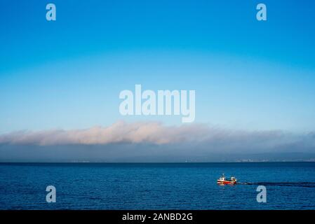 A small fishing boat setting out from Newhaven harbour in Edinburgh on the Firth of Forth. - Stock Photo