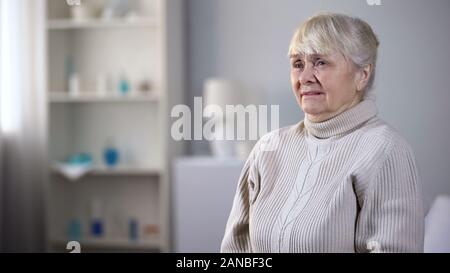 unhappy elderly lady in nursing home sitting on edge of ...