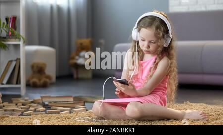 Kid in headphones listening to music on smartphone, addicted to technology - Stock Photo