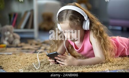 Cute girl absorbed in virtual world of games and music apps on smartphone - Stock Photo