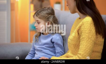 Sad girl turned away from lady, not accepting babysitter, conflict with mother - Stock Photo