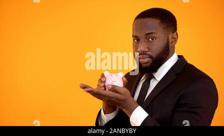 African-american male in formal suit holding piggybank, trustful bank, savings
