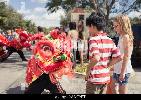 Asian boy and Caucasian girl with dragon at Lunar New Year parade
